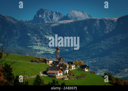Panoramic view of the village and Nikolaus church of Mittelberg with the Langkofel and Plattkofel mountains in the background in South Tyrol - Stock Photo