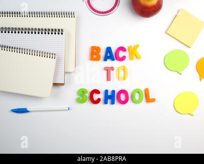 inscription back to school from multi-colored plastic letters and a stack of notebooks with blank white sheets on a white background, top view. - Stock Photo