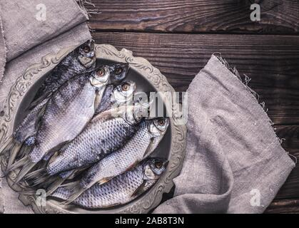 dried salted fish ram in an iron plate on a brown wooden background, top view. - Stock Photo