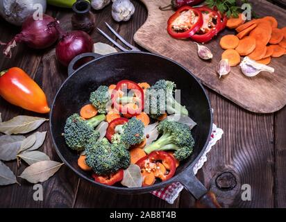 fresh pieces of broccoli, carrots and red peppers in a black cast-iron frying pan on a brown table, top view. - Stock Photo