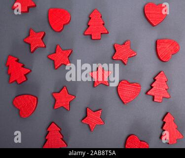black background with red wooden figures of stars, Christmas trees and hearts. - Stock Photo