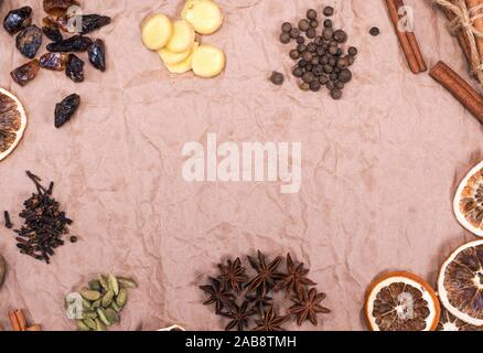 Cloves, ginger slices, cinnamon, star anise, brown sugar, cardamom and dried orange on brown paper, an empty space in the middle. Stock Photo