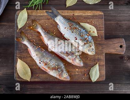 river fish crucian and perch in spices and salt on a brown wooden cutting board. - Stock Photo