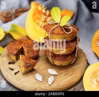 stack of muffins with a pumpkin on a round wooden board and fresh pieces of pumpkin. - Stock Photo