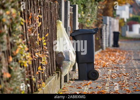 Nuremberg, Germany - November 26, 2019: A yellow bag for plastic waste called Gelber Sack is hanging on a wooden fence in front of a dustbin on a sunn - Stock Photo