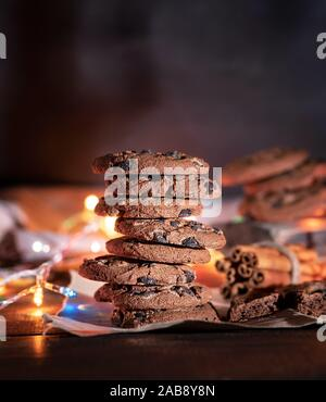 round chocolate cookies in a stack, around the New Year's burning garlands on a brown table. - Stock Photo