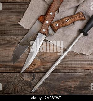 knife with sharpening on the wooden table, top view. - Stock Photo