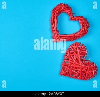 two wicker red hearts on a blue background, copy space. - Stock Photo
