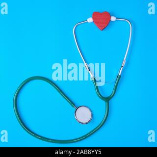 green medical stethoscope and red wooden heart on blue background. - Stock Photo