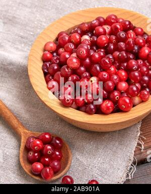 red berries of ripe lingonberries in a wooden bowl on a table, top view.