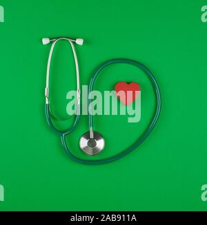medical stethoscope and red wooden heart on green background. - Stock Photo
