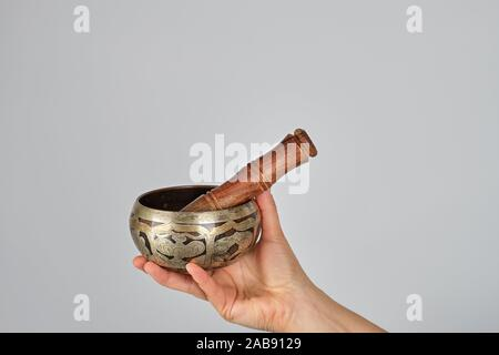 copper singing bowl and wooden stick in female hand on white background. - Stock Photo