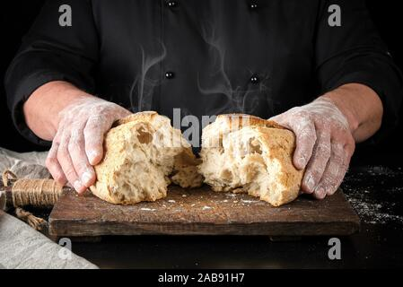 baker in black uniform broke in half a whole baked loaf of white wheat flour bread, hot product lay on a wooden board and steam came out of it. - Stock Photo