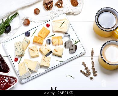 different pieces of cheese on a white wooden board and two yellow cups with a coffee drink, top view. - Stock Photo