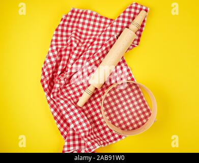 new wooden rolling pin on a red textile napkin and a round sieve for flour, yellow background, top view. - Stock Photo