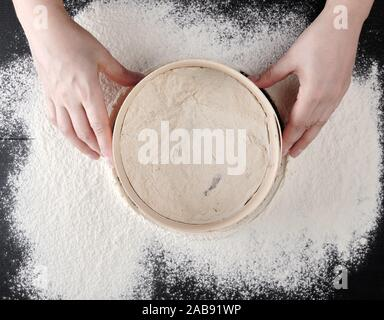 women's hands hold a round wooden sieve and sift white wheat flour, top view. - Stock Photo