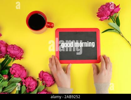 two female hands are holding a black chalk frame with the words good morning, red cup with black coffee and bouquet of peonies on a yellow - Stock Photo