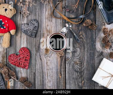 ceramic cup with black coffee and a little teddy bear in a red sweater, gray wooden background, top view. - Stock Photo
