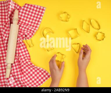 new wooden rolling pin on a red textile napkin and two female hands, yellow background, top view. - Stock Photo