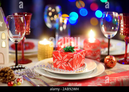 Beautiful table setting for Christmas party or New Year celebration at home. Cozy room with a fireplace and Christmas tree in a background. Xmas time - Stock Photo