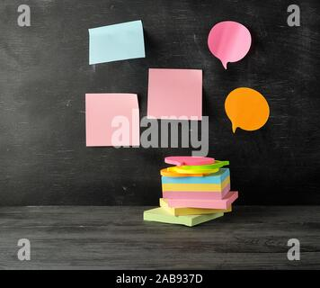 stack of multi-colored sticky stickers on a black wooden background, concept back to school. - Stock Photo