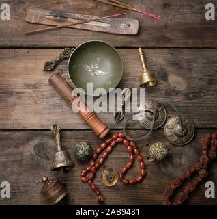Copper singing bowl, prayer beads, prayer drum and other Tibetan religious objects for meditation and alternative medicine on a brown wooden - Stock Photo