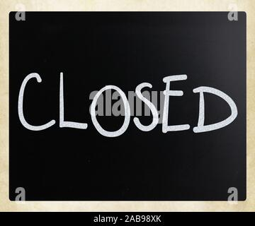 The word ''Closed'' handwritten with white chalk on a blackboard. - Stock Photo