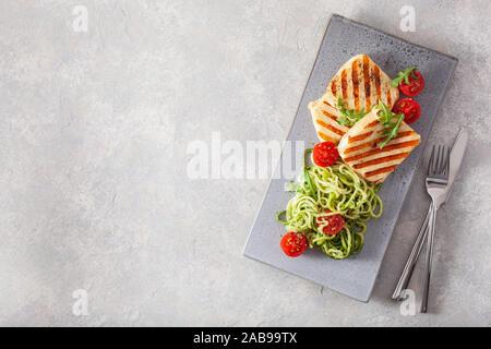ketogenic paleo diet lunch. halloumi cheese, spiralized zucchini with arugula pesto and tomatoes - Stock Photo