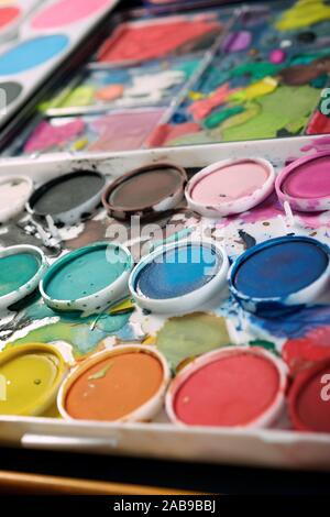 Box of watercolors and brushes on a table. - Stock Photo