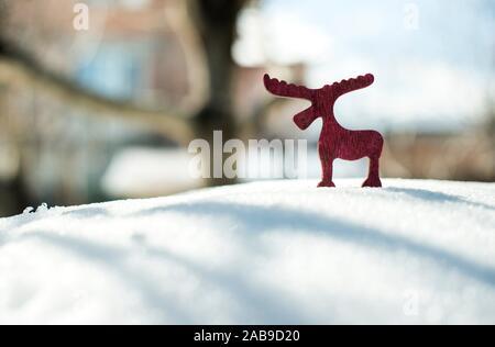 Wooden Christmas deer shape on snow. - Stock Photo