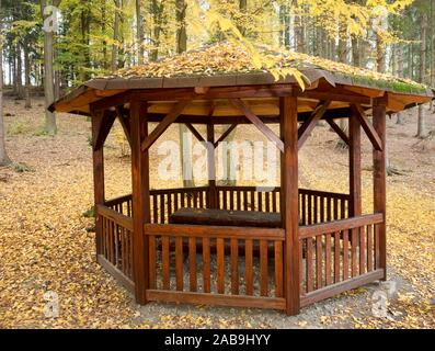 Retro vintage stylized wooden  mountain shelter against sun beams through forest. Traditional wooden construction painted into brown orange colors. - Stock Photo
