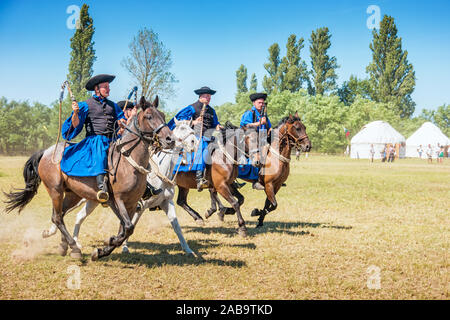 Traditional Hungarian shepherd horsemen ride during the Day of Ancestors tribal assembly in the Hungarian steppe near Bugac, Hungary. - Stock Photo