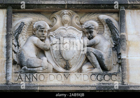 stone carving on a wall in St John's college Oxford part of the university showing two angels or cherubs and the coat of arms of the college from 1900 - Stock Photo