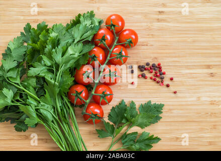 Fresh vegetables on the table, copy space. Food background. Flat lay. Cherry tomatoes, a bunch of parsley, black and red peppers on a wooden chopping