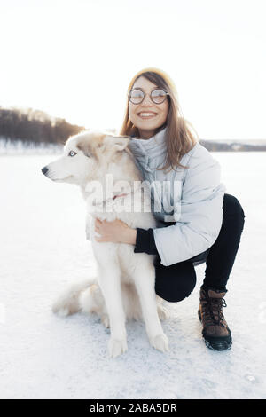 Happy young girl playing with siberian husky dog in winter park. They walk on a frozen lake - Stock Photo