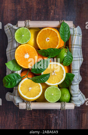 Sliced citrus in a basket on a wooden table. Flat lay. Juicy ripe slices of orange, lemon and lime on a dark brown background. Fruit mix, top view. - Stock Photo