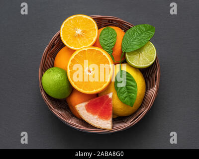 Sliced citrus in a basket on a stone table. Flat lay. Juicy ripe slices of orange, lemon, grapefruit and lime on black background. Fruit mix, top view - Stock Photo