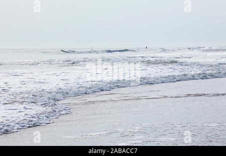 Hazy filtered sunlight hitting waves as they roll in on Ocean City beach where a disant man stands on his stand up paddle board, Ocean City, Maryland, - Stock Photo