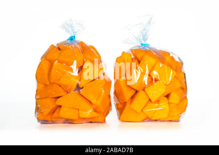 Fresh raw pumpkin pieces in plastic bag ready to be frozen in the refrigerator - Stock Photo