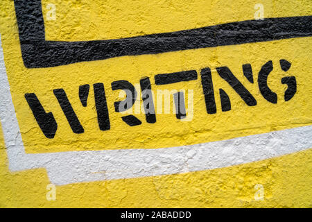 """Fragment of graffiti drawing. Word """"writing"""" in black on yellow old wall decorated with paint in street art style."""