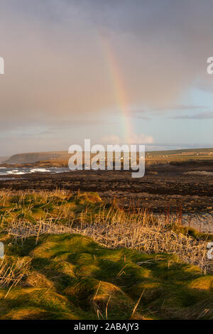 Rainbow over the coast at the Brough of Birsay, Orkney Islands, UK - Stock Photo