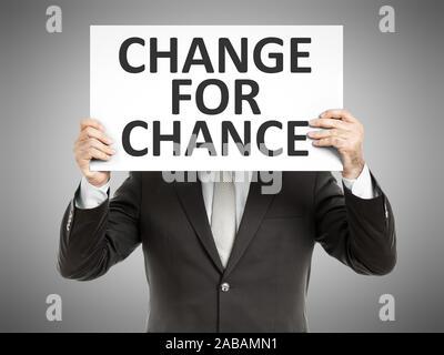 Ein Geschaeftsmann, der ein Schild mit den Worten 'Change for Chance' haelt - Stock Photo
