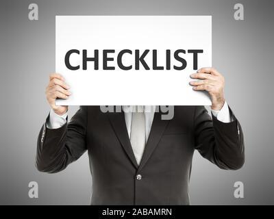 Ein Geschaeftsmann, der ein Schild mit den Worten 'Checklist' haelt - Stock Photo