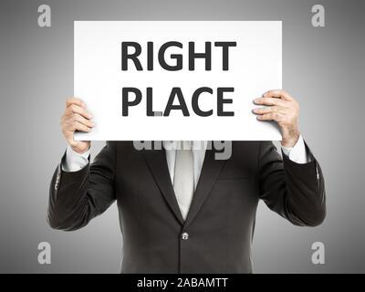 Ein Geschaeftsmann, der ein Schild mit den Worten 'Right Place' haelt - Stock Photo