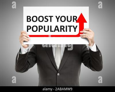 Ein Geschaeftsmann, der ein Schild mit den Worten 'Boost your Popularity' haelt - Stock Photo