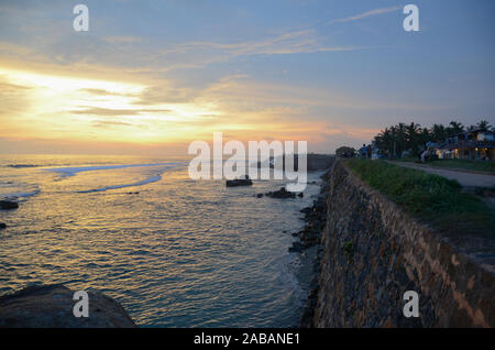 Galle Fort, Sri Lanka - May 04, 2018: View of the stone wall of the city and the ocean at sunset. South-western coast of Sri Lanka - Stock Photo