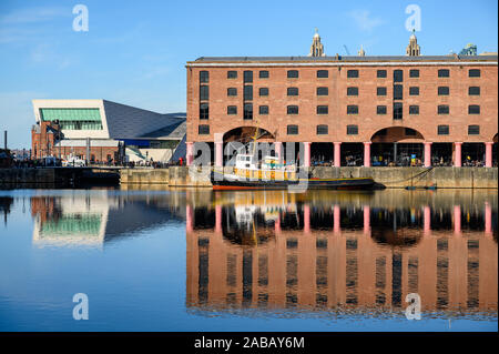 One of the buildings of the Albert Dock, Liverpool, reflected in the water. A boat is moored in front of the building, the Museum of Liverpool is visi - Stock Photo