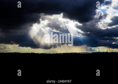 Gray storm clouds through which the rays of the sun - Stock Photo