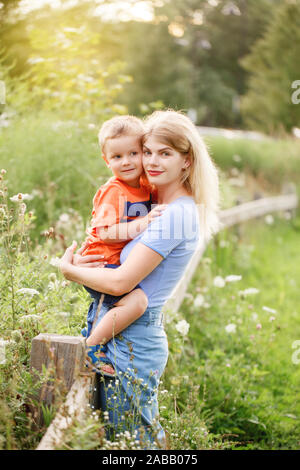 Young blonde Caucasian mother and boy toddler son hugging embracing in park outdoor on summer day. Mom and child love and tenderness. Happy family chi