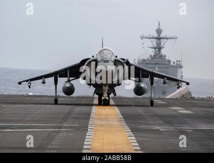 A U.S. Marine Corps AV-8B Harrier II fighter jet lands on the flight deck of the USS Boxer during operations November 19, 2019 in the Pacific Ocean. - Stock Photo